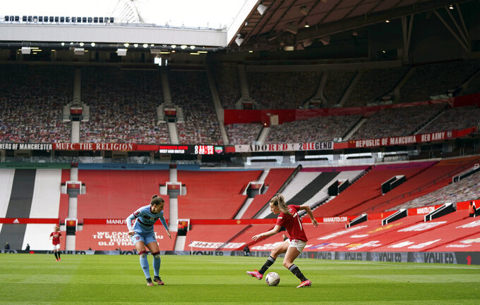 Manchester United's Ella Toone, right, and West Ham United's Cecilie Redisch Kvamme battle for the ball during the Women's Super League match at Old Trafford, Manchester, England, Saturday, March 27, 2021. The Manchester United women's team has made its Old Trafford debut in a league game against West Ham. The team normally plays its Women's Super League home matches at Leigh Sports Village but switched to Old Trafford during the international break in the men's game.  (Zac Goodwin/PA via AP)