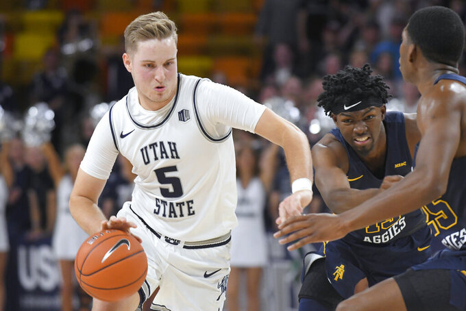 Utah State guard Sam Merrill (5) dribbles as North Carolina A&T guard Kameron Langley, center, and forward Webster Filmore defend during the second half of an NCAA college basketball game Friday, Nov. 15, 2019, in Logan, Utah. (AP Photo/Eli Lucero)