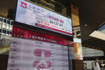 A man walks past a bank's electronic board showing the Hong Kong share index at Hong Kong Stock Exchange Tuesday, Aug. 17, 2021. Asian stock markets declined Tuesday amid concern about turmoil in Afghanistan and unease about China's economic outlook after weak July activity. (AP Photo/Vincent Yu)