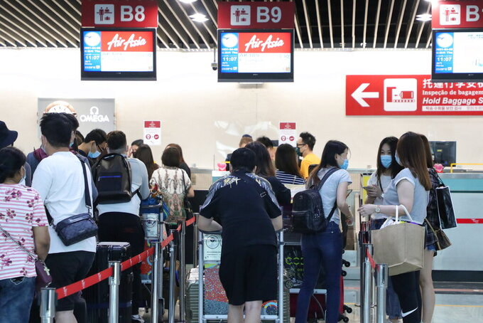 Malaysians and Singaporeans stranded in Macao during pandemic, line up at a check-in counter for the special AirAsia flight to Kuala Lumpur, in Macao airport, Thursday, April 8, 2021. About 50 people of various nationalities boarded a chartered flight from Macao to Malaysia on Thursday after many were stranded for months by the pandemic and border restrictions. (AP Photo)