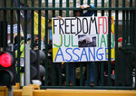 A supporter climbs on a barricade and holds a sign which reads 'Freedom for Julian Assange' as he protests against the extradition of Wikileaks founder Julian Assange outside Belmarsh Magistrates Court in London, Monday, Feb. 24, 2020. The U.S. government and WikiLeaks founder Julian Assange will face off Monday in a high-security London courthouse, a decade after WikiLeaks infuriated American officials by publishing a trove of classified military documents. (AP Photo/Matt Dunham)