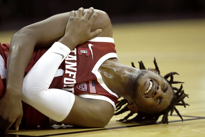Stanford guard Daejon Davis holds his shoulder after getting injured during the first half of an NCAA college basketball game against Oklahoma Monday, Nov. 25, 2019, in Kansas City, Mo. (AP Photo/Charlie Riedel)