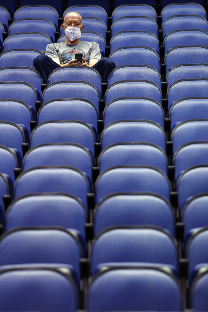 Mike Lemcke, from Richmond, Va., sits in an empty Greensboro Coliseum after the NCAA college basketball games were cancelled at the Atlantic Coast Conference tournament in Greensboro, N.C., Thursday, March 12, 2020. The biggest conferences in college sports all canceled their basketball tournaments because of the new coronavirus, seemingly putting the NCAA Tournament in doubt.  (AP Photo/Ben McKeown)
