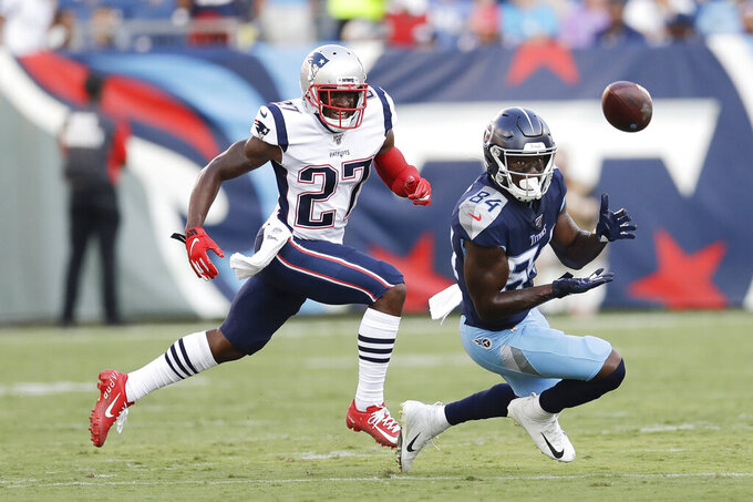 Tennessee Titans wide receiver Corey Davis (84) catches a pass as he is defended New England Patriots defensive back J.C. Jackson (27) in the first half of a preseason NFL football game Saturday, Aug. 17, 2019, in Nashville, Tenn. (AP Photo/James Kenney)