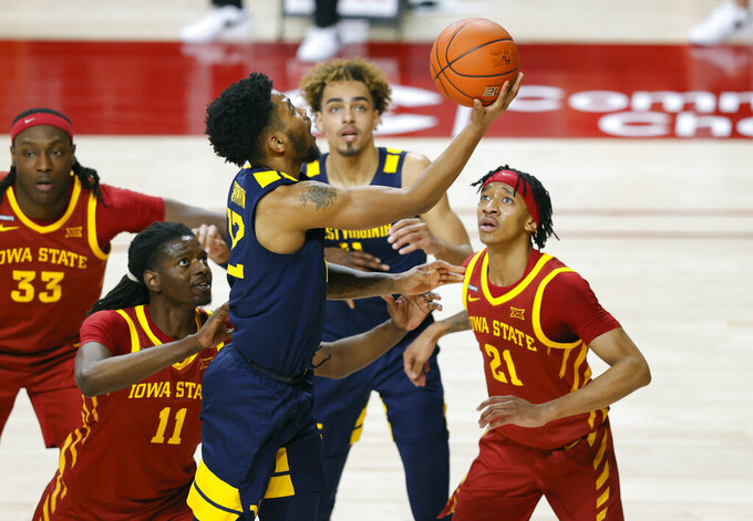 West Virginia guard Taz Sherman, center, leaps for the shot past Iowa State forward Dudley Blackwell, left, and guard Jaden Walker, right, during the first half of an NCAA college basketball game, Tuesday, Feb. 2, 2021, in Ames, Iowa. (AP Photo/Matthew Putney)