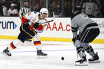 Calgary Flames center Mikael Backlund, left, of Sweden, shoots around Los Angeles Kings defenseman Matt Roy during the first period of an NHL hockey game in Los Angeles, Saturday, Oct. 19, 2019. (AP Photo/Alex Gallardo)