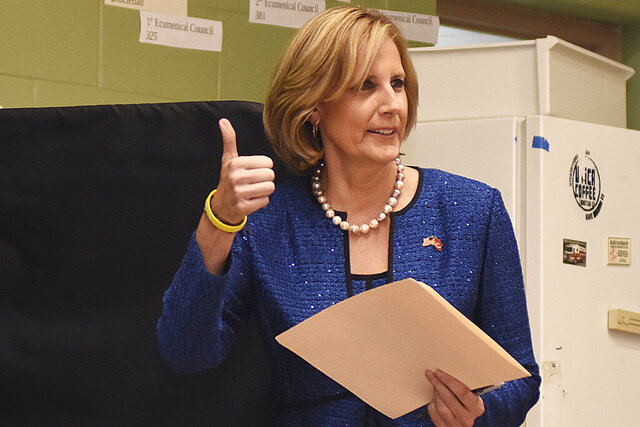 FILE - In this Nov. 6, 2018, file photo, Republican Congresswoman Claudia Tenney signals she successfully cast her ballot after voting at St. George's Church in New Hartford, N.Y. On Tuesday, Dec. 1, 2020, Chenango County informed a state judge it had discovered 55 early voting ballots that weren't canvassed by the local board of election, and therefore weren't included in the vote totals in the ultra-tight race between Tenney and U.S. Rep. Anthony Brindisi.  The most recent results — which don't include those ballots — showed Tenney with a 12-vote lead over Brindisi. (AP Photo/Heather Ainsworth, File)