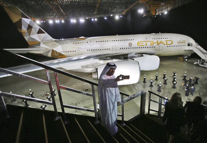 FILE - In this Dec. 18, 2014 file photo, an Emirati man takes a selfie in front of a new Etihad Airways A380 in Abu Dhabi, United Arab Emirates. On Thursday, March 4, 2021, Abu Dhabi's national carrier Etihad  reported core operating losses of $1.7 billion in 2020, reflecting the severe toll of the coronavirus pandemic on the long-troubled airline that has lost billions in recent years. (AP Photo/Kamran Jebreili, File)