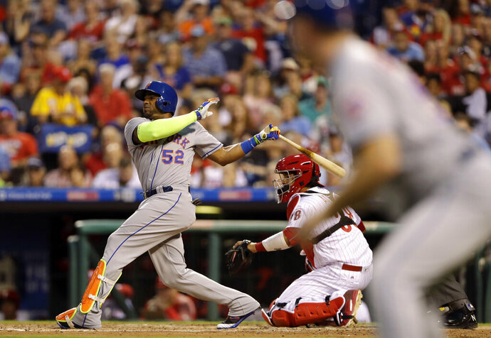 File-This Aug. 11, 2017, file photo shows New York Mets' Yoenis Cespedes, left, following through after hitting a three-run home run as Philadelphia Phillies catcher Jorge Alfaro, center, and third base coach Glenn Sherlock look on during the third inning of a baseball game, in Philadelphia. Cespedes is taking batting practice in his effort to return from a slew of lower-body injuries. Minor league instructor and former Mets player Endy Chavez posted and then deleted video of the 34-year-old Cespedes taking swings Tuesday, Nov. 19, 2019. (AP Photo/Matt Slocum, File)