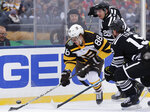 Boston Bruins right wing David Pastrnak (88) controls the puck against Chicago Blackhawks center Jonathan Toews (19) and left wing Brandon Saad (20) in the first period of the NHL Winter Classic hockey game at Notre Dame Stadium, Tuesday, Jan. 1, 2019, in South Bend, Ind. (AP Photo/Nam Y. Huh)