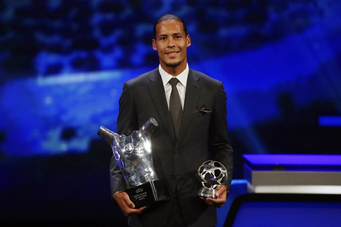 Dutch soccer player Virgil van Dijk of Liverpool holds the award of men's player of the year 2018/19 during the group stage draw at the Grimaldi Forum, in Monaco, Thursday, Aug. 29, 2019. (AP Photo/Daniel Cole)
