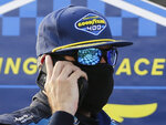 Martin Truex Jr. talks on a cell phone after winning the NASCAR Cup Series auto race at Darlington Raceway, Sunday, May 9, 2021, in Darlington, S.C. (AP Photo/Terry Renna)
