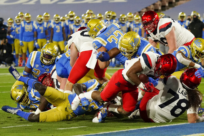 Arizona running back Michael Wiley, right, scores a rushing touchdown during the first half of an NCAA college football game against UCLA, Saturday, Nov. 28, 2020, in Pasadena, Calif. (AP Photo/Marcio Jose Sanchez)