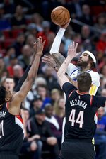 Golden State Warriors center Willie Cauley-Stein, top, shoots over Portland Trail Blazers forward Mario Hezonja (44) and center Hassan Whiteside, left, during the first half of an NBA basketball game in Portland, Ore., Monday, Jan. 20, 2020. (AP Photo/Craig Mitchelldyer)