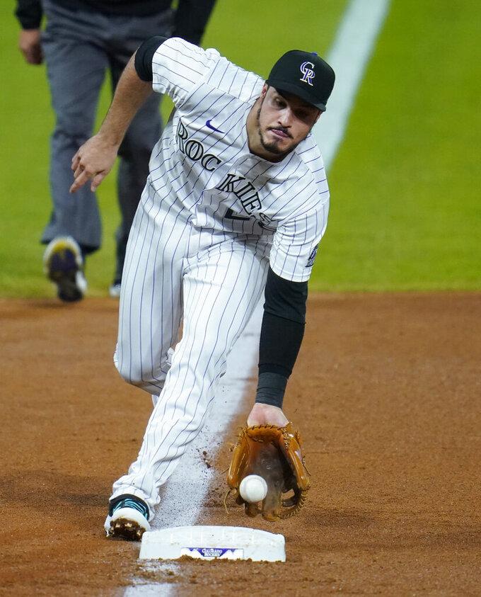 Colorado Rockies third baseman Nolan Arenado picks up a ground ball in the fifth inning of a baseball game Saturday, Sept. 12, 2020, in Denver. (AP Photo/David Zalubowski)