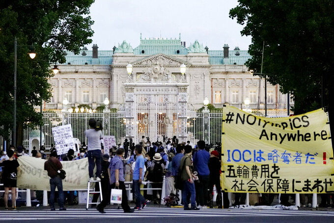 """Protesters against the Tokyo Olympics gather outside Akasaka Palace, Japanese state guest housewhere the welcome party for IOC President Thomas Bach and its officials are held in Tokyo, Japan, Sunday, July 18, 2021. The banner, yellow, reads """"IOC is a looter ! Use Olympic fees for social welfare"""". (Koji Harada/Kyodo News via AP)"""