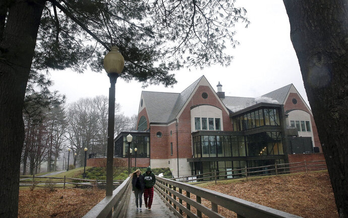In this April 6, 2018 photo, students walk on the campus of Mount Ida College in Newton, Mass. The state attorney general's office said Tuesday, May 15, 2018, that the sale of the college to the University of Massachusetts-Amherst can proceed because UMass paid fair market value for the smaller school, and the only alternative was the bankruptcy and closure of Mount Ida. (Craig F. Walker/The Boston Globe via AP)
