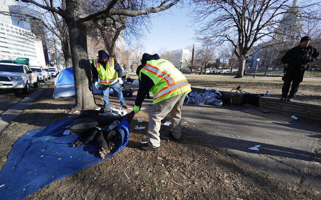 Officials clear a makeshift homeless camp citing a hazard to health early Wednesday, Jan. 15, 2020, in downtown Denver. More than 30 tents had been put up by homeless individuals in a park across from the State Capitol in the past two weeks. The park is being shut down because officials say it's become infested with rats. (AP Photo/David Zalubowski)