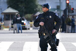 A Capitol Police officer patrols with a rifle at the site where a car crashed into a barrier on Capitol Hill, Friday, April 2, 2021, in Washington. A Capitol Police officer was killed Friday after a man rammed a car into two officers at a barricade outside the U.S. Capitol and then emerged wielding a knife.(AP Photo/Jacquelyn Martin)