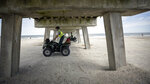 Georgia Department of Natural Resources law enforcement division Corporal Barry Britt, foreground, and DNR Game Warden Chandler Hamrick patrol Tybee Island, Ga., beaches on ATVs after Gov. Bryan Kemp signed an executive order allowing people to exercise outside, with social distancing of at least six feet because of the coronavirus outbreak. (Stephen B. Morton/Atlanta Journal-Constitution via AP)