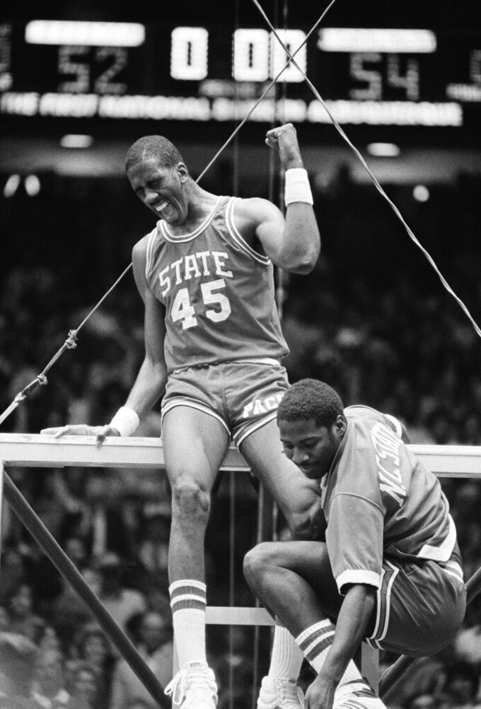 FILE - In this early Tuesday, April 5, 1983, file photo, North Carolina center Cozell McQueen (45) yells while standing on the rim after defeating Houston 54-52 to win the NCAA college basketball championship in Albuquerque, N.M.  Joining McQueen on the rim is teammate Ernie Myers. There are still moments, even after nearly four decades, when Ernie Myers has trouble believing it all really happened for his North Carolina State team. (AP Photo/File)