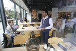 Klatch Coffee owner Bo Thiara, center, talks with customer Daniel Karel after giving Karel a tasting of Elida Natural Geisha coffee at his shop in San Francisco, Wednesday, May 15, 2019. The California cafe is brewing up what it calls the world's most expensive coffee - at $75 a cup. A few lucky coffee lovers got to try free samples Wednesday at the San Francisco branch, where promotional signs are on display advertising,