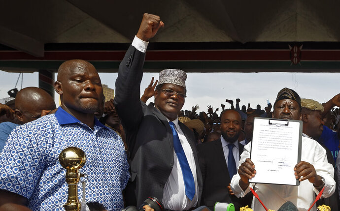 FILE - In this Tuesday, Jan. 30, 2018 file photo, opposition politician Miguna Miguna, center, raises his fist as a gesture to the crowd as he stands next to opposition leader Raila Odinga, right, as Odinga holds an oath during a mock