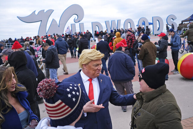 Tim Carney, dressed as President Donald Trump, center, talks with people near the boardwalk before the start of a campaign rally in Wildwood, N.J., Tuesday, Jan. 28, 2020.  (AP Photo/Seth Wenig)
