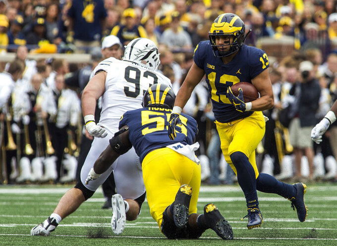 Michigan running back Tru Wilson (13) rushes behind a block from offensive lineman James Hudson (55) in the third quarter of an NCAA college football game against Western Michigan in Ann Arbor, Mich., Saturday, Sept. 8, 2018. Michigan won 49-3. (AP Photo/Tony Ding)
