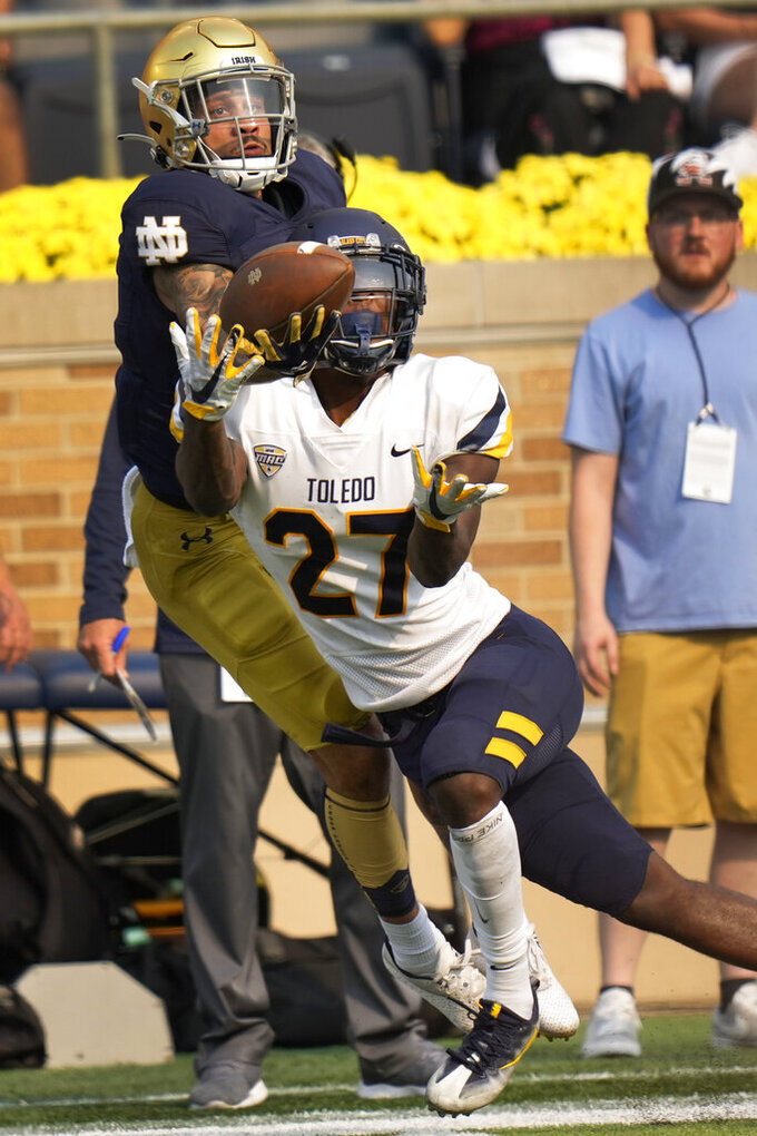 Toledo cornerback Quinyon Mitchell (27) battle for a pass with Notre Dame wide receiver Braden Lenzy (0) in the second half of an NCAA college football game in South Bend, Ind., Saturday, Sept. 11, 2021. Notre Dame won 32-29. (AP Photo/AJ Mast)