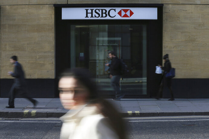 FILE - In this Nov. 2, 2015, file photo, a person walks past a branch of HSBC near Liverpool Street Station in London.  Europe's biggest bank has reported its net profit jumped 30 percent in 2018 from the previous year to $12.6 billion. (AP Photo/Tim Ireland, File)