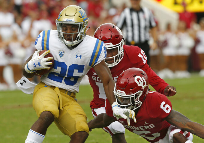 Oklahoma safety Patrick Fields (10) and cornerback Tre Brown (6) move in to tackle UCLA running back Martell Irby (26) in the second half of an NCAA college football game in Norman, Okla., Saturday, Sept. 8, 2018. Oklahoma won 49-21. (AP Photo/Sue Ogrocki)