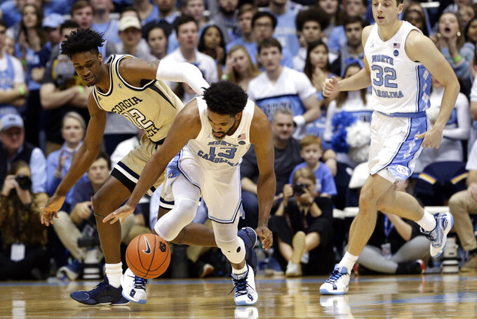Georgia Tech forward Khalid Moore, left, and North Carolina guard Jeremiah Francis (13) chase the ball while North Carolina guard Justin Pierce (32) watches during the first half of an NCAA college basketball game in Chapel Hill, N.C., Saturday, Jan. 4, 2020. (AP Photo/Gerry Broome)