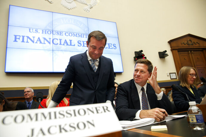 FILE - In this Sept. 24, 2019, file photo, Securities and Exchange Commission (SEC) Chairman Jay Clayton, center, waves to a commissioner as he takes his seat between SEC Commissioners Robert Jackson Jr., left, and Hester Peirce, at the start of a House Financial Services Committee hearing on Capitol Hill in Washington. With little fanfare, the SEC is taking steps to revamp one of the government's most successful whistleblower programs, alarming advocates who warn the changes will set back efforts to police Wall Street and punish corporate fraud (AP Photo/Jacquelyn Martin, File)
