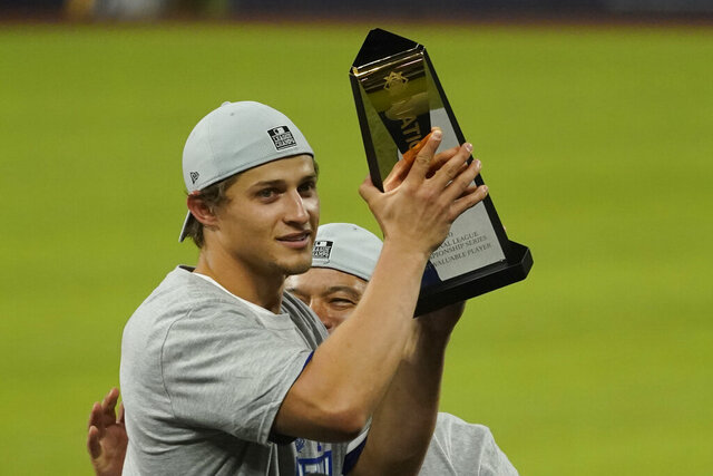 Los Angeles Dodgers shortstop Corey Seager celebrates with the MVP trophy after winning Game 7 of a baseball National League Championship Series against the Atlanta Braves Sunday, Oct. 18, 2020, in Arlington, Texas. (AP Photo/Eric Gay)