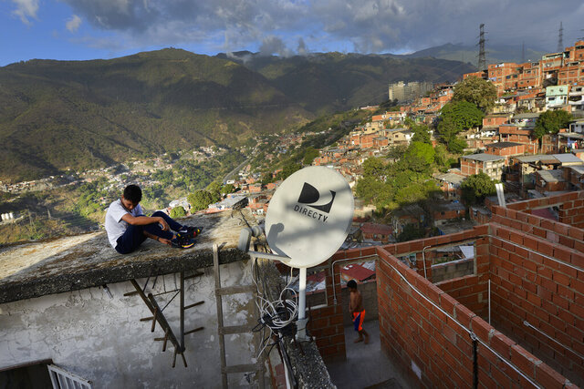 FILE - In this  Jan. 9, 2020 file photo, a DirectTV dish stands on home in the Catia neighborhood of Caracas, Venezuela. AT&T, one of the last major American companies still operating in Venezuela, said Tuesday, May 19, 2020 it will immediately abandon Venezuela's pay TV market, as U.S. sanctions prohibit its DirecTV platform from broadcasting channels that it is required to carry by the Venezuelan government, making it impossible to comply with the legal requirements of both countries. (AP Photo/Matias Delacroix, File)