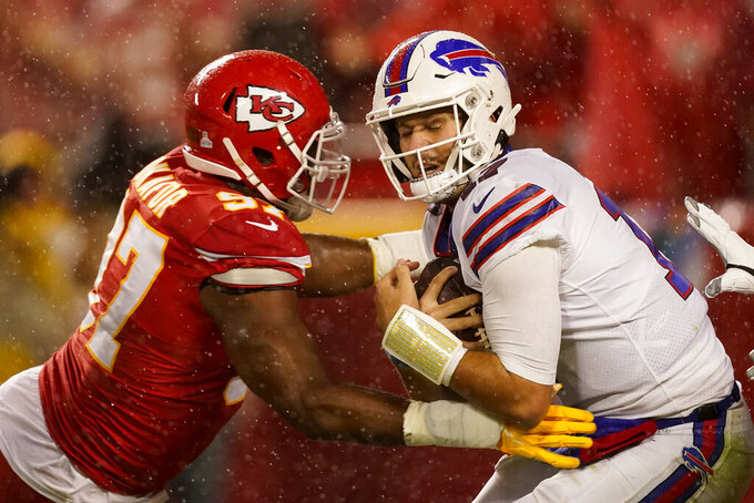 Buffalo Bills quarterback Josh Allen, right, is slowed by Kansas City Chiefs defensive end Alex Okafor (97) during the second half of an NFL football game Sunday, Oct. 10, 2021, in Kansas City, Mo. (AP Photo/Charlie Riedel)