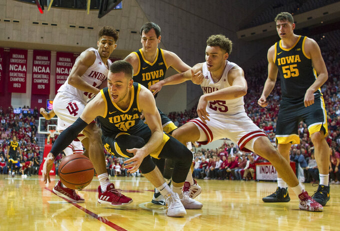 Iowa guard Connor McCaffery (30) falls on the ball during the second half of an NCAA college basketball game against Indiana, Thursday, Feb. 13, 2020, in Bloomington, Ind. (AP Photo/Doug McSchooler)