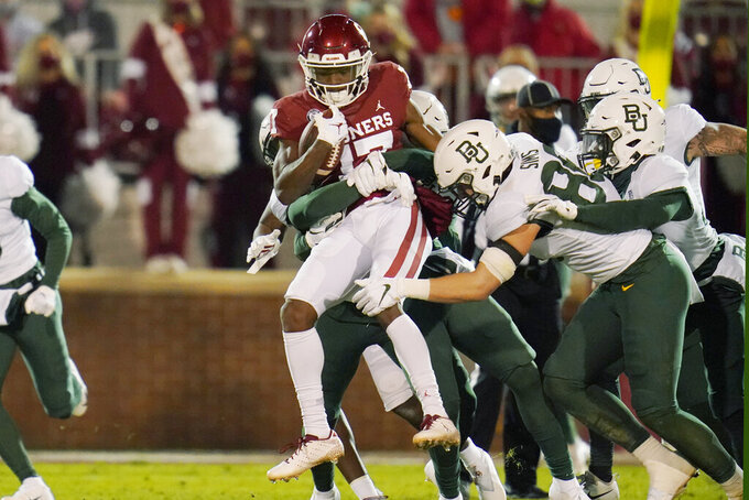 Oklahoma wide receiver Marvin Mims, left, is tackled by Baylor safety Al Walcott, rear, and tight end Ben Sims, right, in the first half of an NCAA college football game Saturday, Dec. 5, 2020, in Norman, Okla. (AP Photo/Sue Ogrocki)
