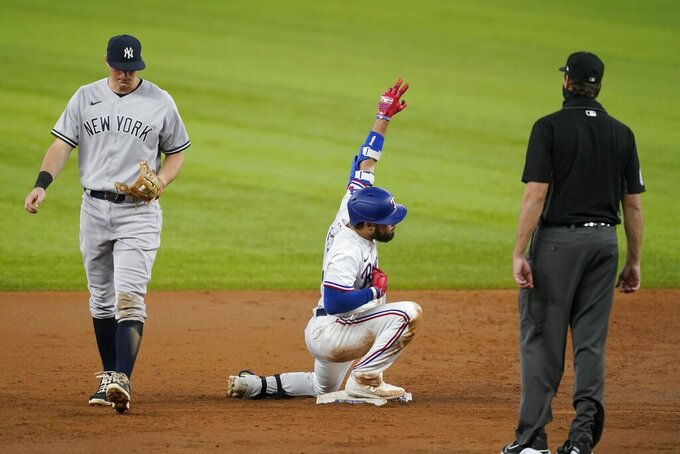 New York Yankees second baseman DJ LeMahieu, left, walks past and umpire Ryan Additon, right, looks on as Texas Rangers' Isiah Kiner-Falefa, center, celebrates his run-scoring double in the second inning of a baseball game in Arlington, Texas, Monday, May 17, 2021. Rangers' David Dahl scored on the hit. (AP Photo/Tony Gutierrez)