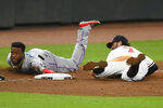 Miami Marlins' Monte Harrison, left, and Atlanta Braves shortstop Dansby Swanson look to the umpire after Swanson tagged out Harrison for a double play at third base during the ninth inning of a baseball game Monday, Sept. 21, 2020, in Atlanta. (AP Photo/John Amis)