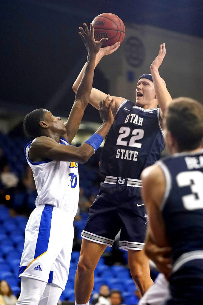 San Jose State guard Omari Moore (10) blocks a shot by Utah State guard Brock Miller (22) during the first half of an NCAA college basketball game Wednesday, Dec. 4, 2019, in San Jose, Calif. (AP Photo/Tony Avelar)