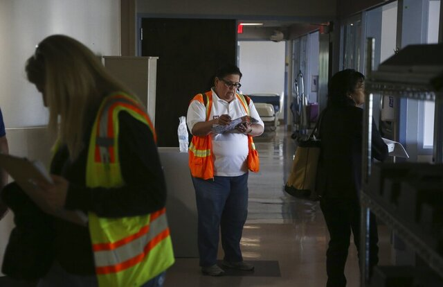 Patricia Vasquez, middle, from the U.S. Army Corps of Engineers, takes notes as she and fellow colleagues join staffers from the Arizona health department as they tour the currently closed St. Luke's Medical Center hospital to see the viability of reopening the facility for possible future use due to the coronavirus Wednesday, March 25, 2020, in Phoenix. (AP Photo/Ross D. Franklin)