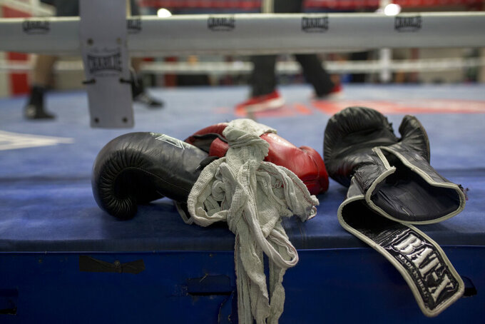 FILE - In this Friday, April 29, 2016 file photo, boxing gloves lie on a boxing ring as boxers work out at El Rayo boxing gym in Madrid, Spain. Journeymen fighters like Jamie Quinn regularly rack up losses in British boxing. They're hired to fight up-and-comers who are unbeaten or looking to bolster their resumes. Wins are few and far between. The 30-year-old Quinn has a record of seven wins, 104 losses and two draws. He has fought and lost twice since boxing events returned from the pandemic stoppage. (AP Photo/Francisco Seco, File)