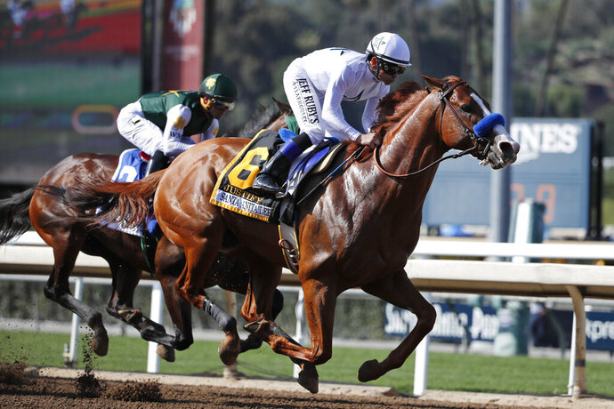 FILE - In this April 7, 2018, file photo, Justify, ridden by Mike Smith, gallops past Bolt d'Oro, left, with jockey Javier Castellano, during the Santa Anita Derby horse race at Santa Anita in Arcadia, Calif. Justify won the race, and Bolt d'Oro came in second. The New York Times says Justify won the 2018 Triple Crown after a failed postrace drug test at Santa Anita that could have kept the horse out of the Kentucky Derby. The newspaper reported Wednesday, Sept. 11, 2019, that Bob Baffert-trained Justify tested positive for the drug scopolamine after winning the Santa Anita Derby. Justify went on to win the Derby and took the Preakness and Belmont stakes to complete the Triple Crown. (AP Photo/Jae C. Hong, File)
