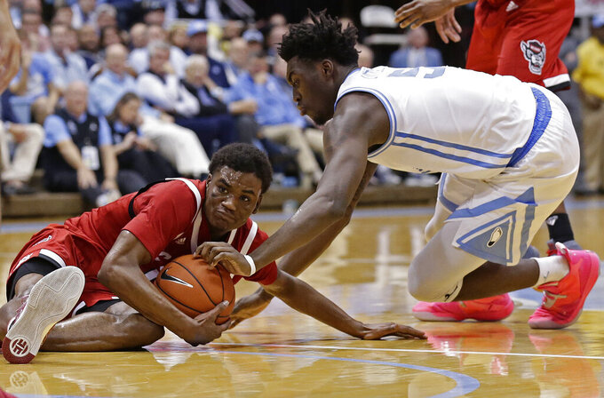 North Carolina's Nassir Little, right, and North Carolina State's Markell Johnson fall to the floor for a loose ball during the second half of an NCAA college basketball game in Chapel Hill, N.C., Tuesday, Feb. 5, 2019. (AP Photo/Gerry Broome)