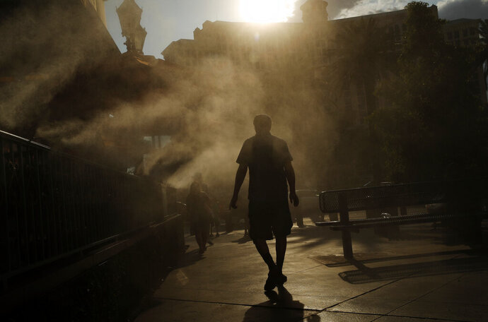 File - In this July 26, 2018, file photo, a man cools off in a water mist along the Las Vegas Strip in Las Vegas. Planners in Las Vegas say they're working to reduce rising temperatures in a city where paved areas create a warmer environment than plant-covered or rural desert areas. The Las Vegas Sun reports that a panel on Oct. 15, 2019, considered a recent Urban Land Institute finding that Las Vegas is the most intense