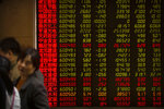 Chinese investors monitor stock prices at a brokerage house in Beijing, Friday, April 19, 2019. Asian stock indexes rose moderately in quiet holiday trading on Good Friday as some markets were closed. (AP Photo/Mark Schiefelbein)
