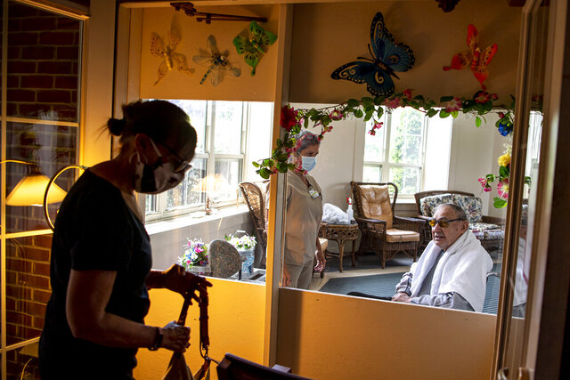 In a Wednesday, June 10, 2020 photo, Ellen Jones, of McCandless, prepares to sit down to visit her father Elliott Tanack, a resident of the Jewish Association on Aging's Charles Morris Nursing and Rehabilitation Center, through a plexiglass barrier at the facility, in Squirrel Hill, Pa. (Alexandra Wimley/Pittsburgh Post-Gazette via AP)