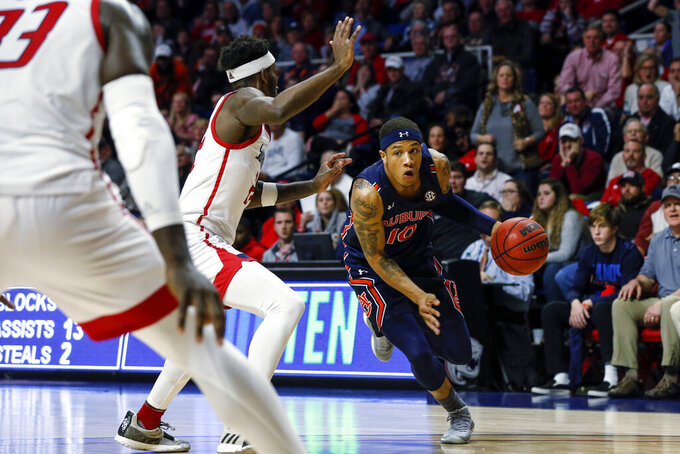 Auburn guard Samir Doughty (10) drives to the basket around South Alabama guard Andre Fox (22) during the second half of an NCAA college basketball game, Tuesday, Nov. 12, 2019, in Mobile, Ala. Auburn won 70-69. (AP Photo/Butch Dill)